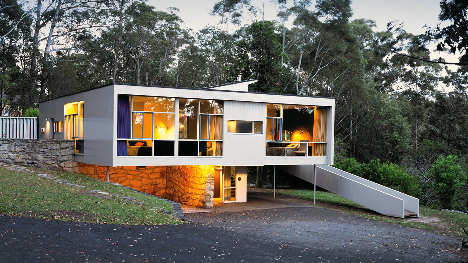 Rose Seidler House in bush landscape, internals are well lit with gold lights