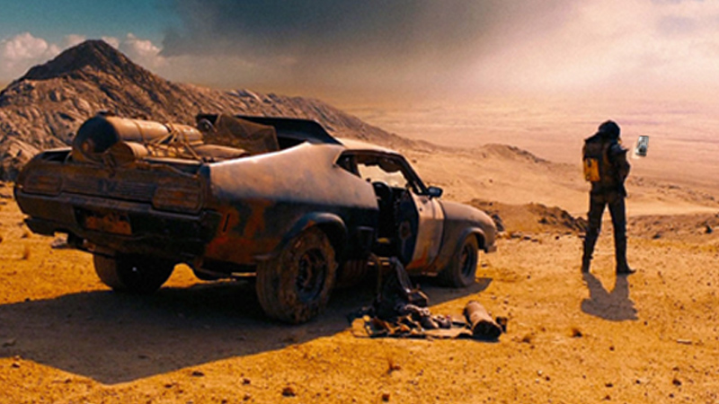 Mad Max poster, protagonist holds phone next to rusty old car