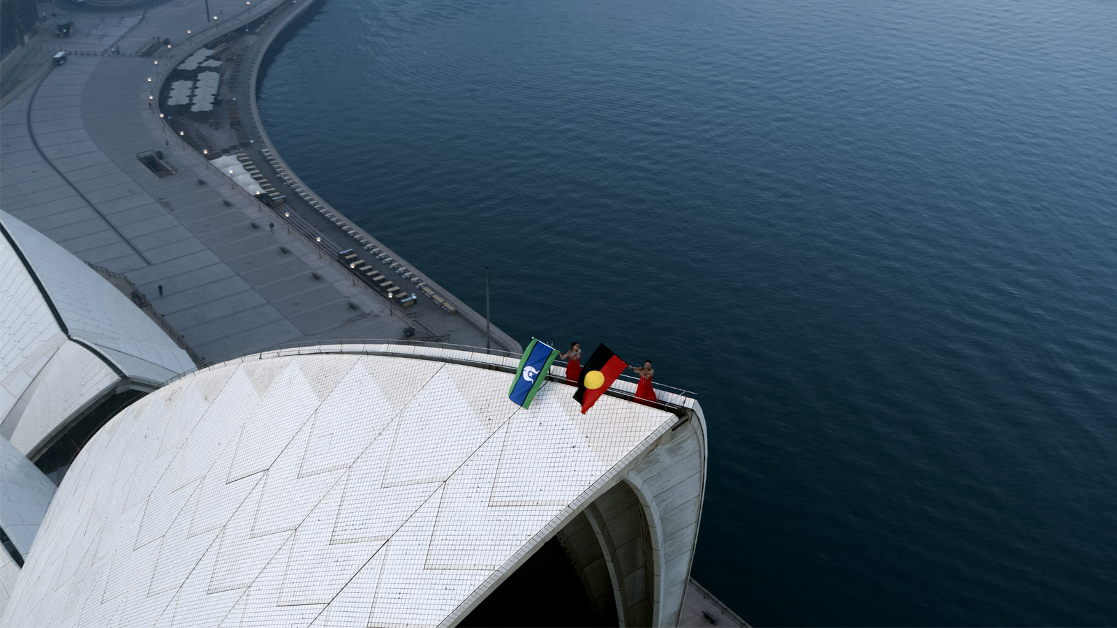 Two dancers wave Aboriginal and Torres Strait Islander flags on top of the Opera House sails